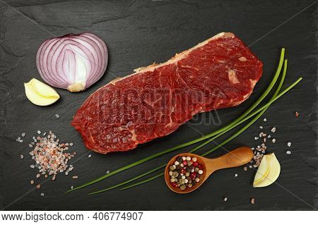One Raw Beefsteak Red Meat Cut, Spices, Peppercorn In Wooden Scoop, Green Spring Chive, Onion, Garli