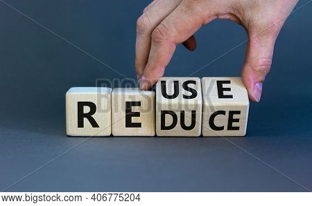 Reuse Or Reduce Symbol. Businessman Turns Wooden Cubes And Changes The Words Reduce To Reuse. Beauti