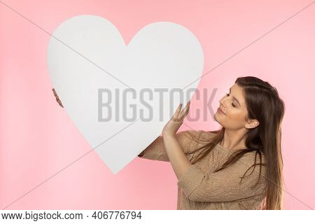 A Beautiful Girl In Love Holds A Heart Shape In Her Hand. Young Woman Wants To Give A Beautiful Hear