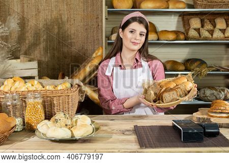 In A Traditional Bakery, The Saleswoman Advertises The Latest Type Of Bread. A Young And Attractive