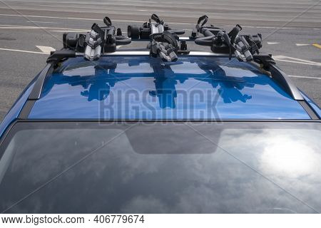3 Bicycle Racks Mounted On Blue Car Roof.