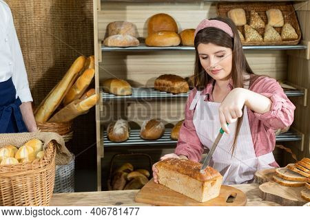 Before The Arrival Of Customers, The Baker Corrects The Arrangement Of The Bread And The Young Sales