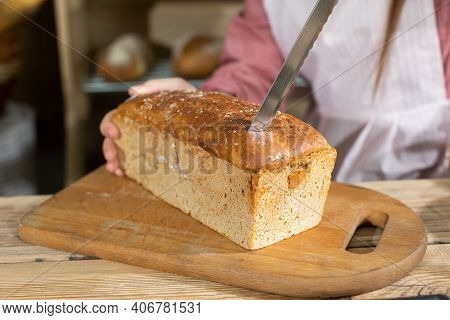 Up Close, You Can See A Young Girl Starting To Cut A Loaf Of Bread With A Sharp, Clove Knife. He Cut