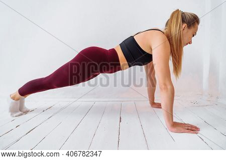 Young Beautiful Athletic Girl In Leggings And Top Making An Exercise Plank. Healthy Lifestyle. A Wom