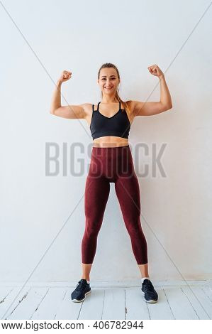 Attractive, Muscular Fitness Girl Sits Against A White Wall With A Happy, Smiling Face And Shows Her