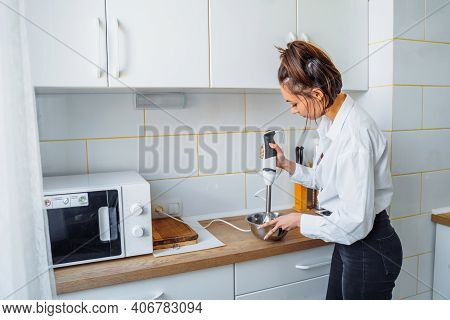 Attractive Girl Preparing Dough In A Food Processor While Standing In A Bright Kitchen. Mixing Dough