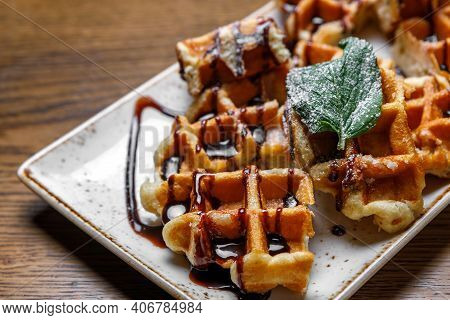 Freshly Baked Shortbread Waffles, Drizzled With Chocolate, Decorated With Basil Leaves, Served On A
