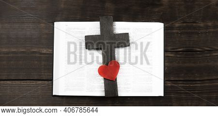 Open Bible Book On A Wooden Table. Wooden Cross Of Jesus. Red Heart. The Concept Of Loving God\'s Wo