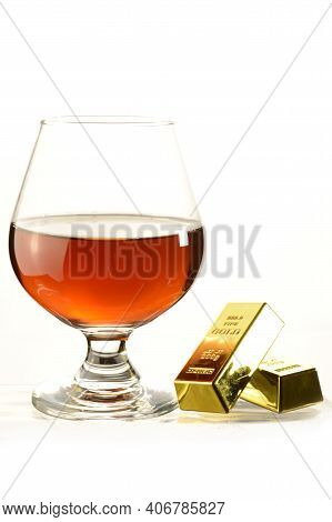 A Glass Of Cognac And Gold Bullion Bars Over A White Background.