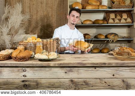 A Clerk Sits Behind The Counter Serving His Own Baked Goods. A Handsome Baker Serves His Customers I