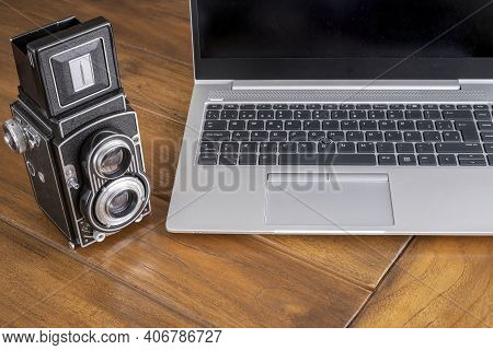 A Modern Laptop Computer Next To An Antique Twin Lens Camera, Contrasting Between Modern And Retro S