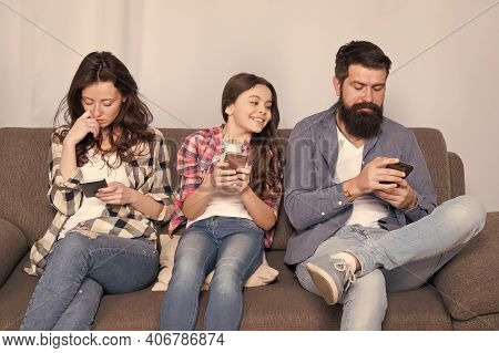 Mom Dad And Daughter Relaxing On Couch. Family Spend Weekend Online. Child Little Girl Use Smartphon