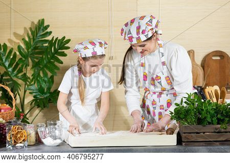 The Girls, I.e. Mom And Daughter, Toss And Toss The Dough Together On The Dough To Further Reduce Th