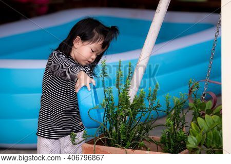 Cute Girl Help Their Parents With Chore Housework. Asian Children Use A Blue Bowl To Scoop Water In