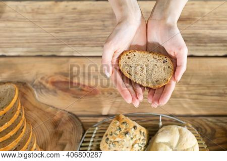 Young Hands Protectively Hold One Slice Of Wheat Bread. After Donating One Slice Of Bread To The Nee