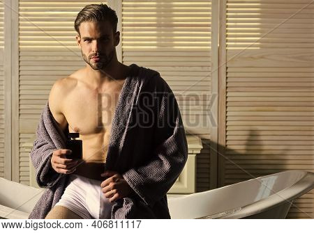 Man With Muscular Torso In Underwear And Bathrobe On Bath. Guy With Perfume Bottle In Bathroom