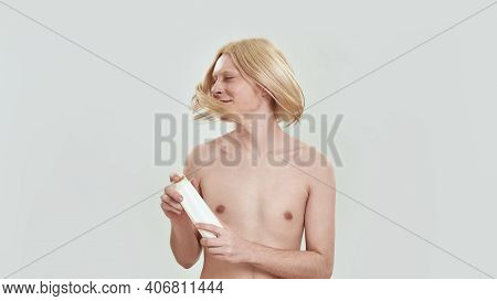 Happy Young Caucasian Man Shaking Long Blond Hair While Holding Shampoo Bottle And Smiling On White
