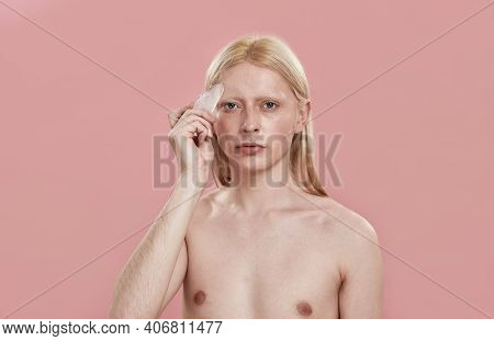 Young Caucasian Man With Long Blond Hair Using Quartz Massager On Forehead While Standing On Pink Ba