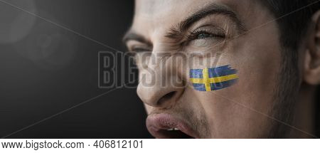 A Screaming Man With The Image Of The Sweden National Flag On His Face