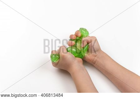 Toy Slime In The Hands Of A Child On A Light Background. The Child Plays With Mucus And Develops Fin
