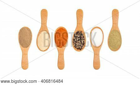 Six Flavoring On A Wooden Spoon On A White Background.