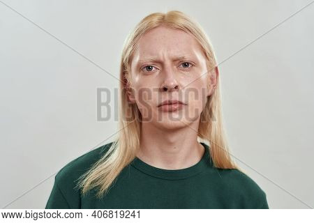 Portrait Of Gloomy Young Caucasian Fair Hair Guy Looking At Camera While Posing On Light Background,