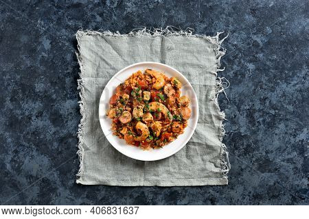 Creole Jambalaya With Smoked Sausages, Chicken Meat And Vegetables On Plate Over Blue Stone Backgrou