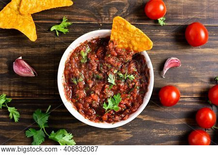 Homemade Tomato Salsa In Bowl Over Wooden Background. Top View, Flat Lay