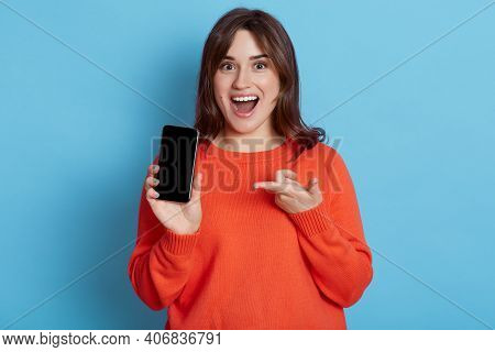 Portrait Of Surprised Woman In Casual Clothing Showing Blank Screen Of Mobile Phone Isolated Over Bl