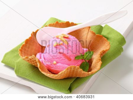 pink ice cream scoop with almonds, in the waffle bowl with the spoon