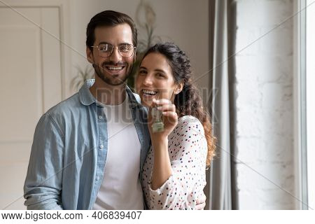 Portrait Of Happy Newlyweds Homeowners Looking At Camera Showing Keys