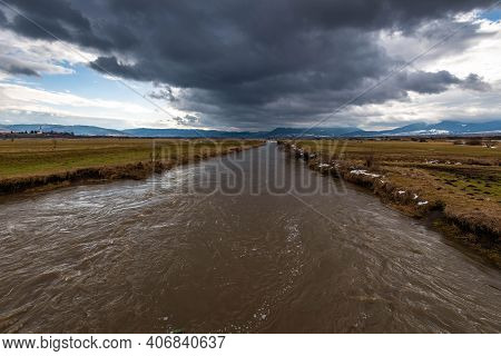 Dirty Flooded Olt River Wide Angle View, Dramatic Dark Storm Clouds In The Background.
