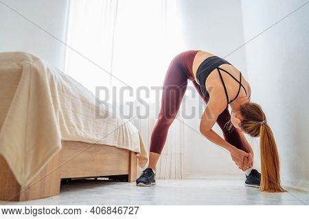 Beautiful Pumped Up Girl Is Doing Sports Training At Home. She Tilting To Different Legs And Leaning