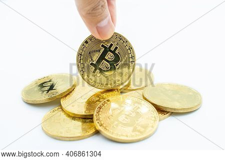Someone Finger With Stack Of Golden Bitcoin Isolated On White Background. Bitcoin Is One Of The Popu