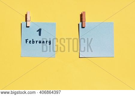 1st Of February. 1st Day Of The Month, Calendar Date. Two Blue Sheets For Writing On A Yellow Backgr