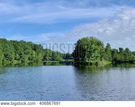 Freshwater Wilderness Lake With Unrecognizable Fishing Boat In The Background With Blue Skies And Gr