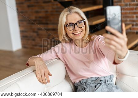 Sanguine Cheerful Middle-aged Woman Takes A Selfie On The Smartphone Spending Leisure Time At Home.