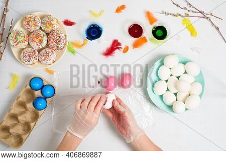 The Process Of Coloring Eggs For Easter In Blue And Red Colors. A Woman In Gloves Paints Eggs With D
