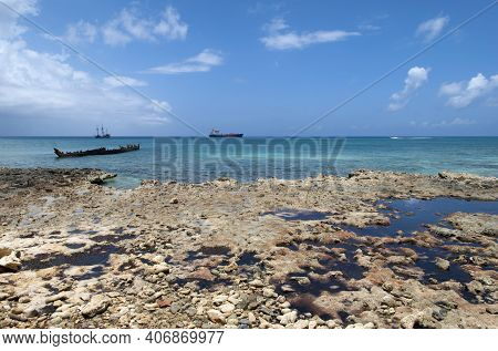 The View Of A Rocky Seven Mile Beach On Grand Cayman Island With A Sunken Ship In A Background (caym
