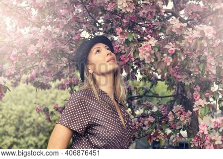 Portrait Of A Beautiful Woman Among Spring Foliage And Flowers