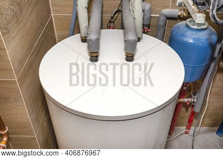 Water Tank For A Modern Gas Boiler In The Home Boiler Room Lined With Ceramic Tiles.