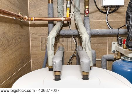 Water Tank And Gas Pipes For A Modern Gas Boiler In A Home Boiler Room, Lined With Ceramic Tiles.