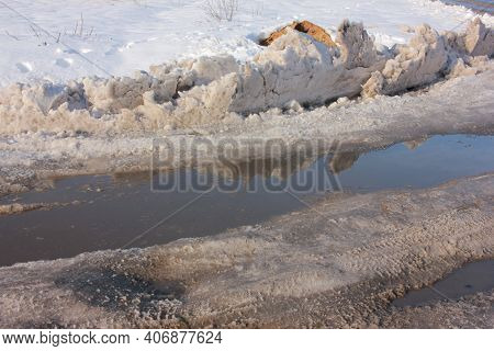Slush On Road From Melting Snow, And A Large Puddle On The Road. Sunny Spring Day.