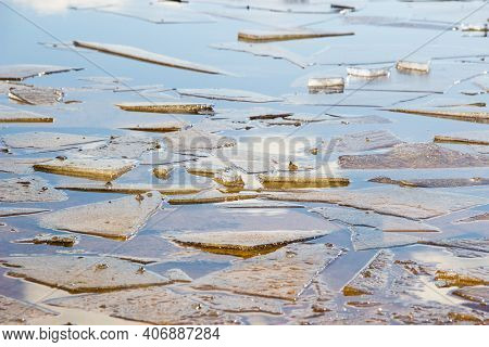 Ice Drift On A River With Blue Water. White Snow Broken Ice Full Of Hummocks In It And Sun Reflectio