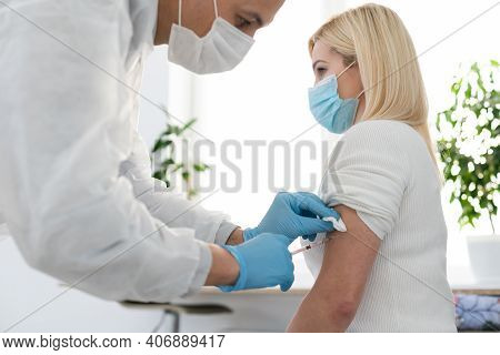 Hand Of Medical Staff Injecting Coronavirus Covid-19 Vaccine In Vaccine Syringe To Arm Muscle Of Cau
