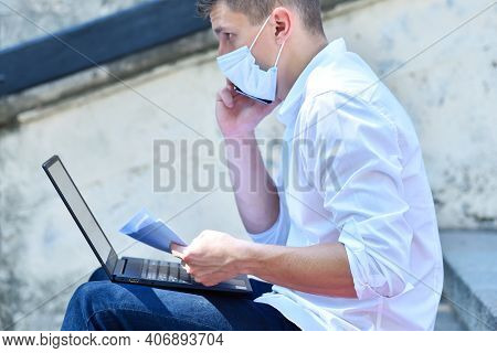 Financial Analyst In Mask Working Outdoor And Speaks On Mobile Phone. Pandemia And Coronavirus Conce