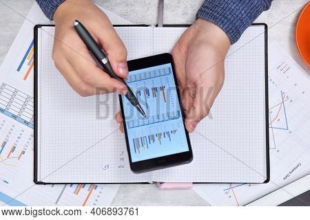 Businessman Hands Using Smart Phone With Financial Document. Money And Trade Concept. Close Up