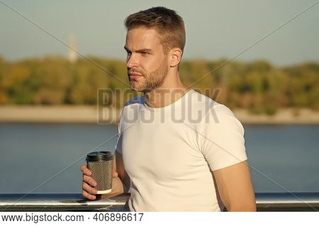 Simple Summer Joy. Young Guy Enjoy Drinking Coffee On River Bank. Handsome Man Hold Hot Cup Outdoors