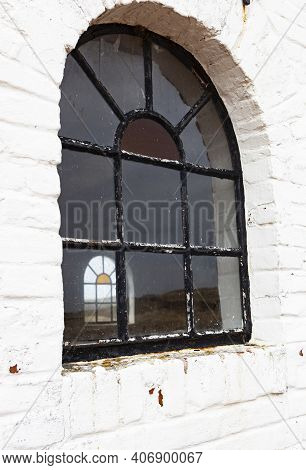 The Photo Shows An Old And Weathered Barn Window With White Brick Wall