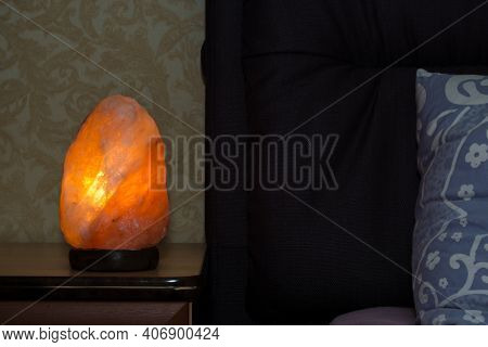 Himalayan Pink Salt Lamp On The Bedside Table In The Bedroom.
